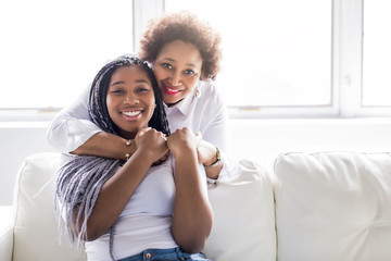 affectionate mother and daughter sitting on sofa