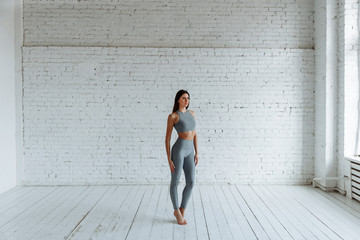 Young slim brunette woman in a yoga outfit. Healthy lifestyle in the fitness club