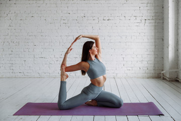 Young attractive smiling woman practicing yoga, sitting in One Legged King Pigeon exercise, Eka Pada Rajakapotasana pose, working out, wearing sportswear, grey pants, bra, indoor full length, home