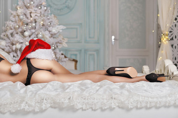 Beautiful sexy Santa Clause in elegant panties, hat and bra. Fashion portrait of model girl indoors with christmas tree. Cute woman in lace black lingerie. Female ass in underwear. Naked body