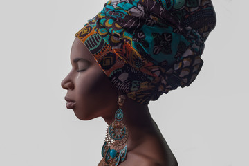 Young beautiful African woman in traditional style with scarf, earrings crying, isolated on gray background. racism, depression or loneliness concept..