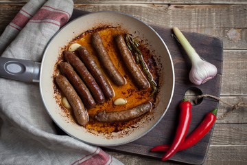 Grilled lamb sausage with rosemary and garlic in a frying pan in olive oil.