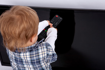 Cute toddler boy trying to turn on the TV with a remote control