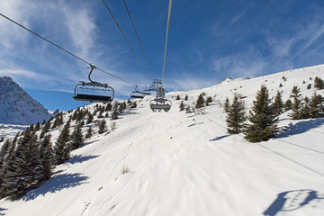 Panoramic view of an alpine mountainside with ski lift