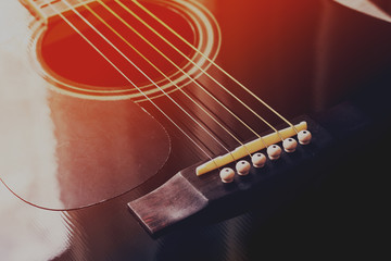Black acoustic guitar, red-blue toned photo