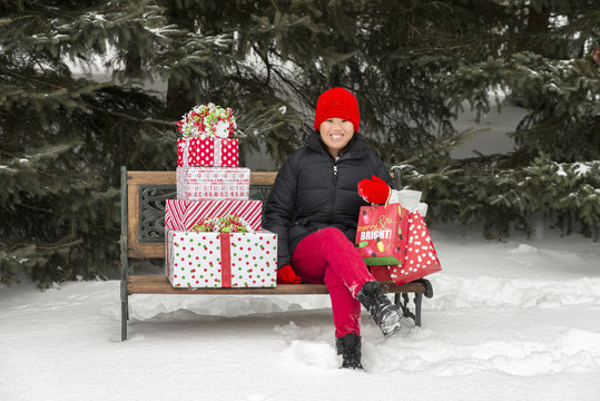 Asian Girl on bench with Christmas presents