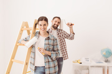 Happy couple painting their new home