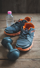 Running shoes dumbbell and drinking water bottle on wooden background