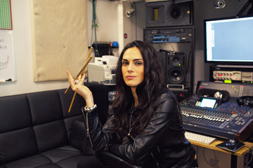 Young woman holding drumsticks in a recording studio