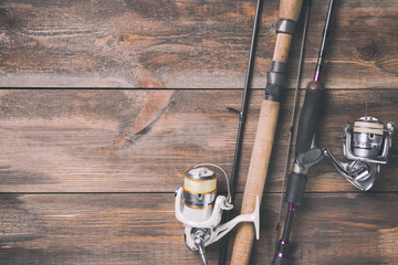 Fishing rods and reels with line on wooden background with free space. Toned image