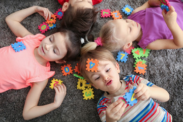 Cute little children playing with colorful figures while lying on carpet at home