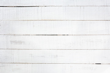 Old wooden planks painted with white paint cracked by a rustic background
