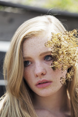 Close up of young woman with dry flowers outdoors