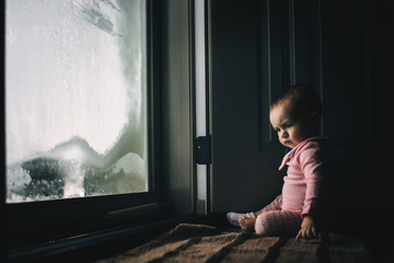 Girl siting by door at home