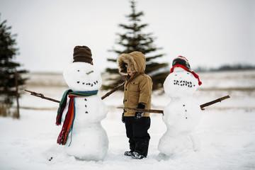 Boy standing by snowmen on field against sky