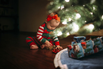 Girl playing with toy while sitting by Christmas tree at home