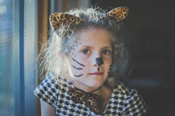 Portrait of girl with face paint sitting by window at home