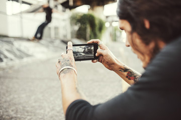 Man taking picture through smartphone outdoors