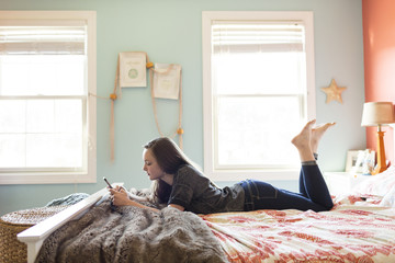 Side view of woman using mobile phone while lying on bed at home