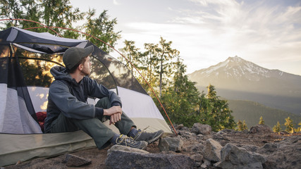 Male hiker looking away while sitting in tent against sky