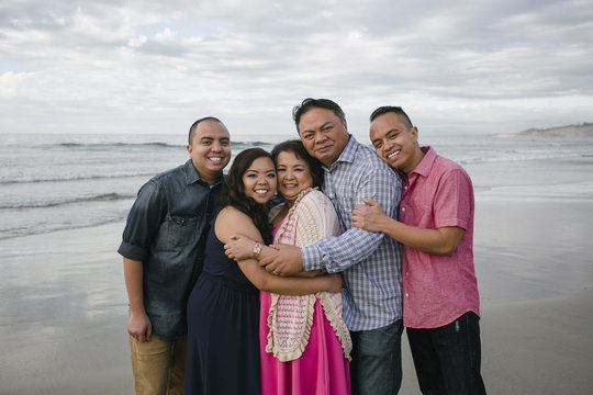 Portrait of happy family standing on sea shore at beach