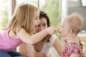 Mother looking at girl feeding food to sister at home