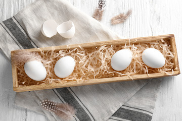Wooden tray with eggs and eggshell on napkin