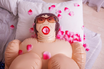 Inflatable sex doll strewed with petals of roses.