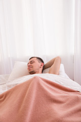 Satisfied man under a blanket and masturbates