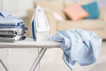 Electric iron and pile of clothes on ironing board