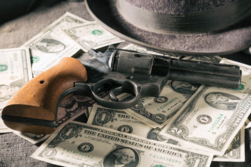 Crime concept. Black gun with dollar banknotes and hat. Toned image