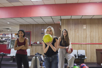 A young woman bowling with friends.