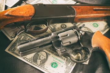 Mafia concept. Black gun with shotgun on dollar banknotes. Toned image