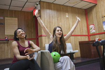 Two young women chereing at a bowling alley.