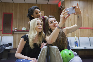 Two young woman taking a picture on a cell phone.