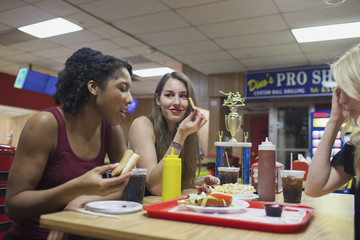 Young women eating at a diner together.