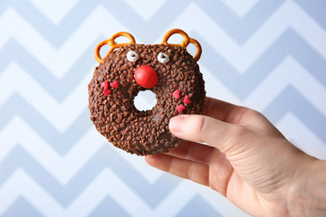 Female hand holding creative donut on color background