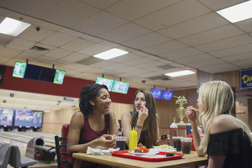 Three young women eating at a diner.