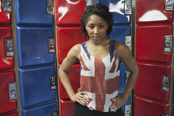 A young woman posing in front of red and blue lockers.