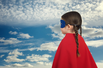 Cute little super hero girl in the red cloak. Superhero concept