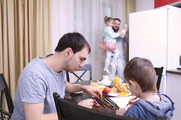 Male gay couple with children having breakfast in kitchen