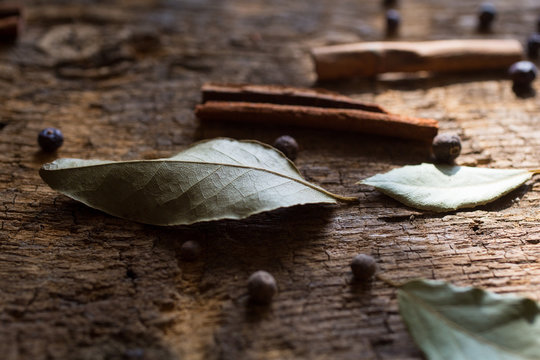 Laurel leaves, cinnamon sticks and juniper berries on wood