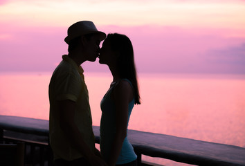 Man and woman kissing at sunset. Romantic getaway concept.