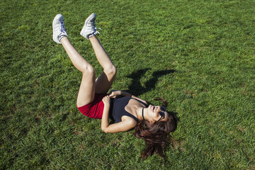 Cheerful young woman lying on grass