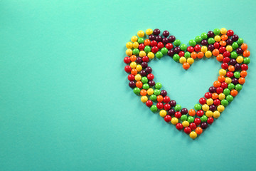 Colorful candies in shape of heart on color background
