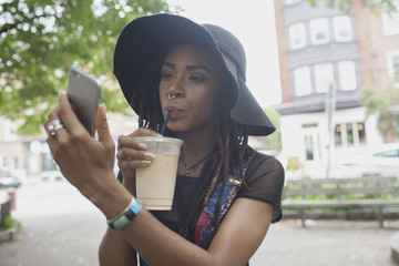 A young woman taking a photograph whilst drinking an iced coffee.
