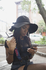 Young woman holding coffee while using smartphone outdoors