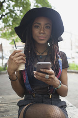 Portrait of young woman holding coffee and using smartphone outdoors