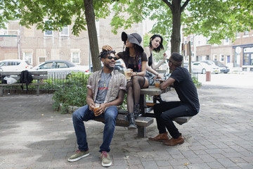 Four young adults sitting on a picnic table.