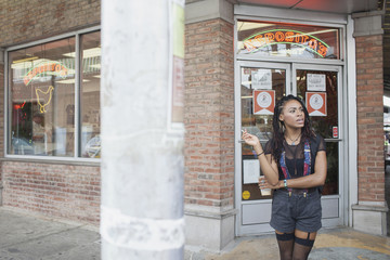 A young woman waiting outside a store.